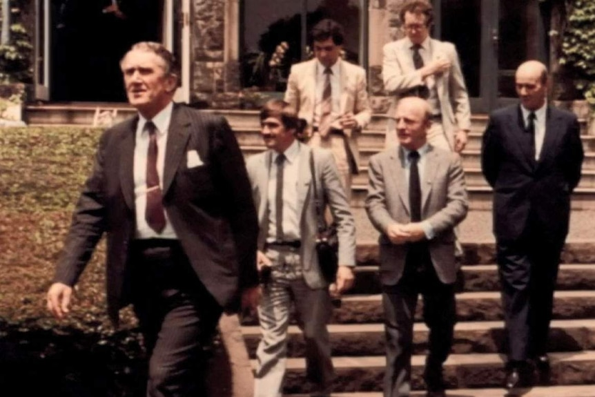 Barrie Cassidy with tape recorder on shoulder following Malcolm Fraser with other journalists.