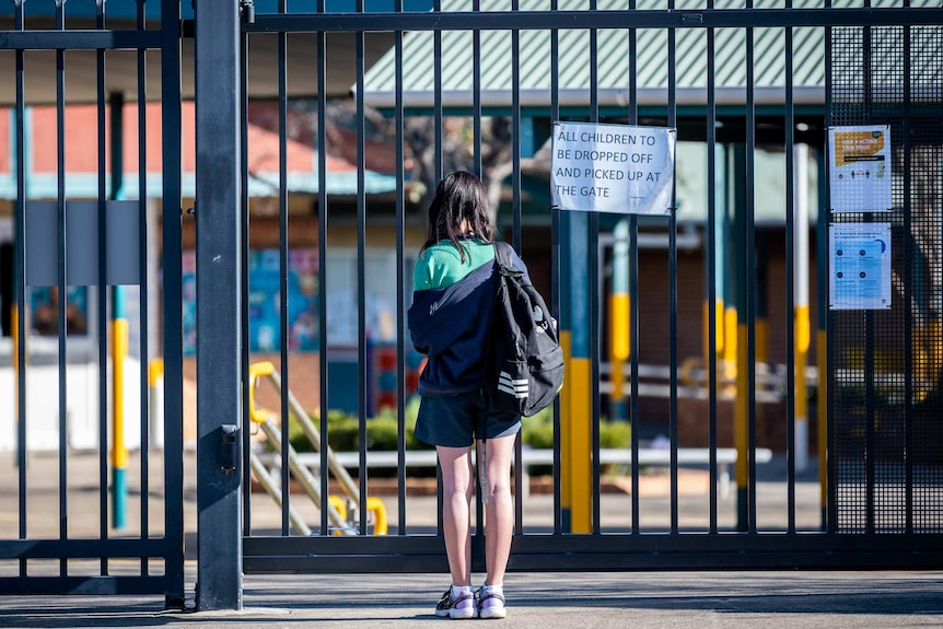 a young girl standing at the gates of an empty school