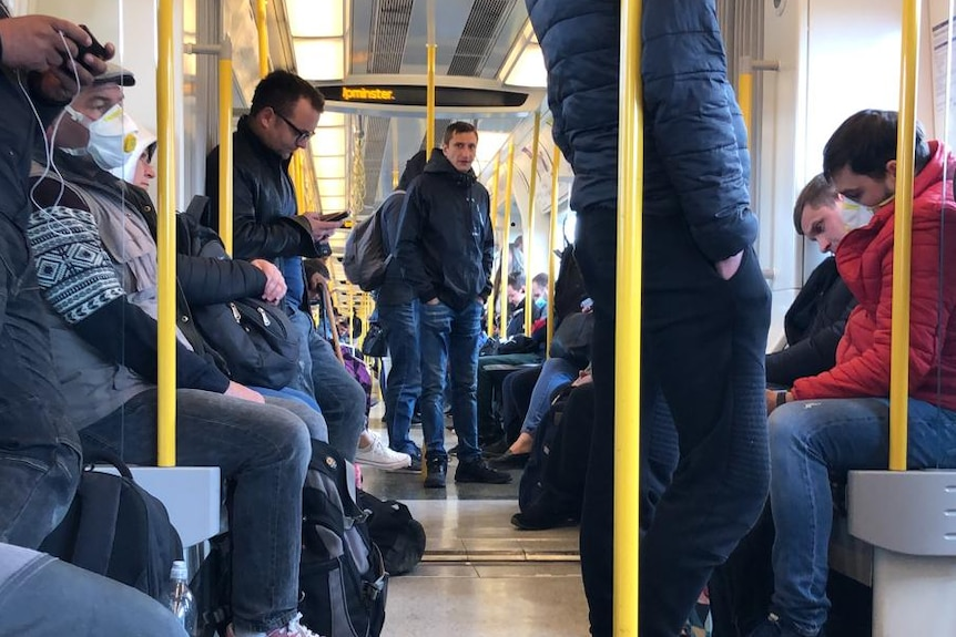People stand and sit down on a train.