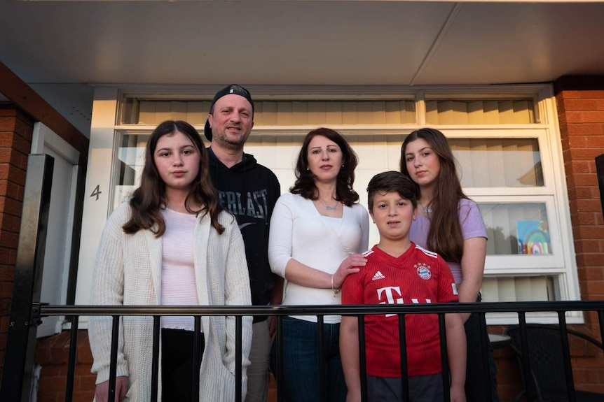 A family stand outside their home