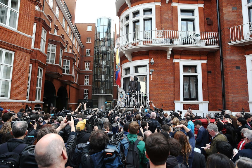 Julian Assange speaks to a crowd of people on the balcony of the Embassy of Ecuador in London.
