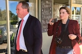 Barnaby Joyce walks in front of Vikki Campion walk past a Family First campaign poster in a shop window.