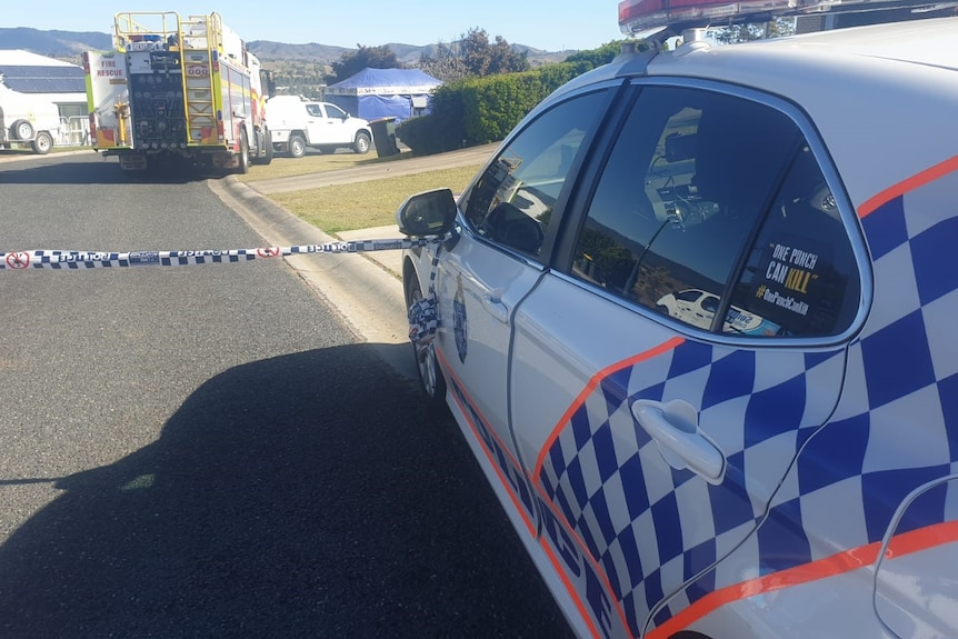 The side of a police car in front of police tape and a fire engine in the background.