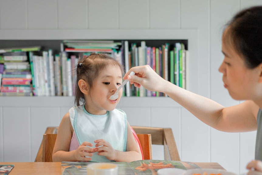 Woman feeding young child with a spoon sitting at a table.