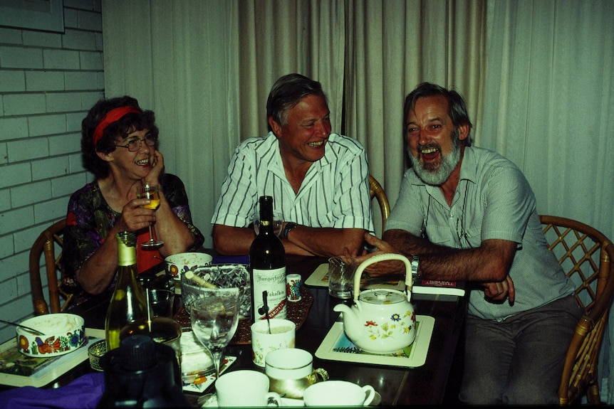 Two men and a woman sit at a table together laughing.