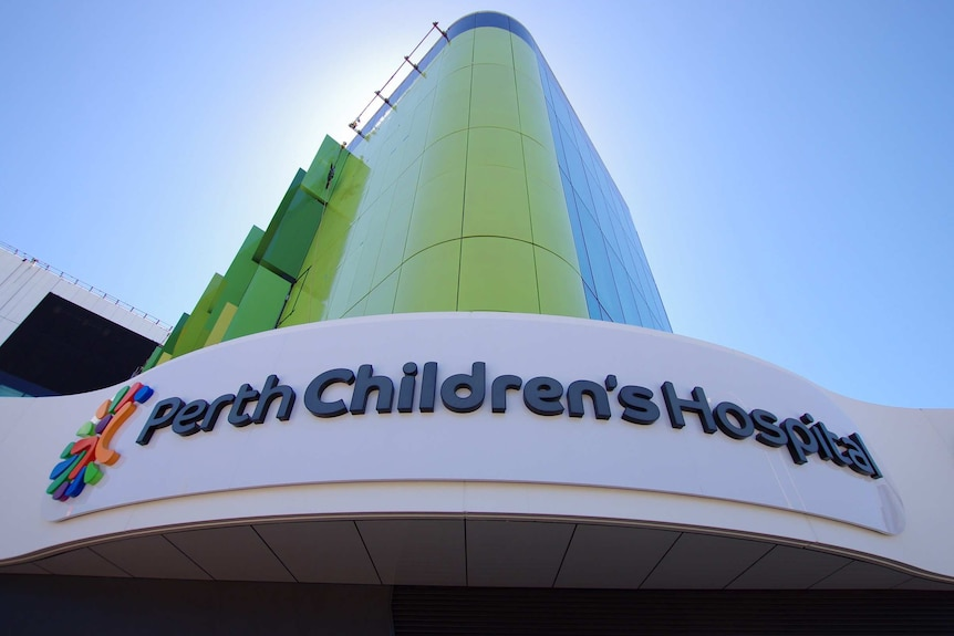 A shot from the ground of a Perth Children's Hospital sign and green building.