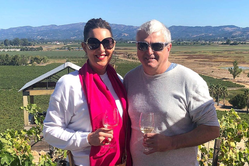 A woman and a man smile while holding wine glasses with a vineyard in the background.