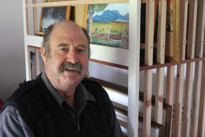 Albany man, Tony Davis, in front of shelves containing the work of renowned Noongar artist, Bella Kelly.