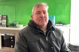 A man wearing a leather jacket and hoodie sits in front of a green wall in a kitchen.