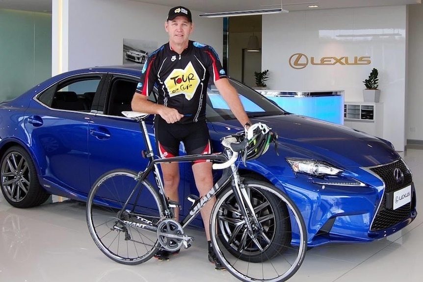 A man next to a bike and car