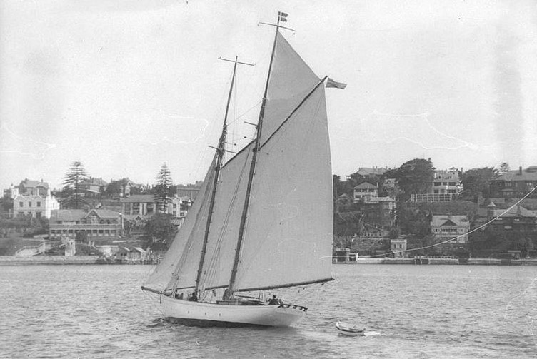 Black and white photo of a gaff rigged schooner under sail towing a dinghy, with a foreshore and houses behind it.