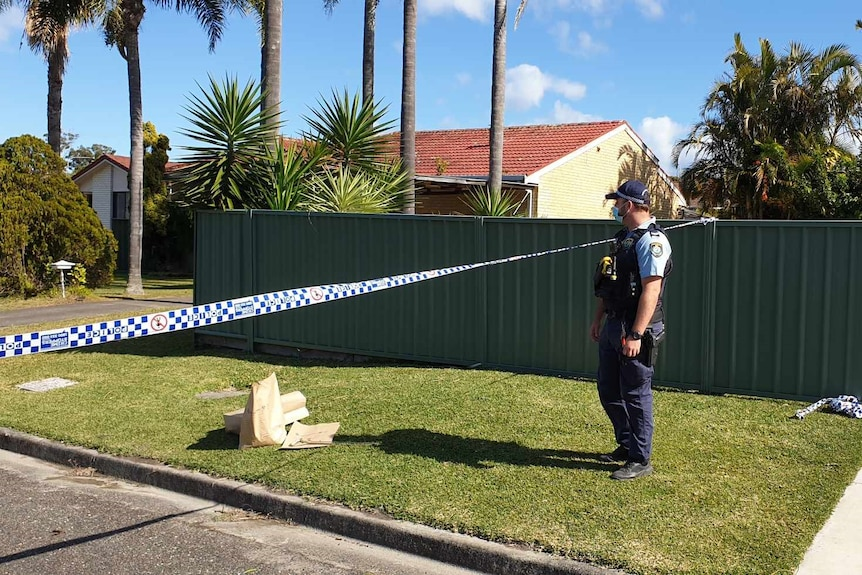 A policeman in uniform stands outside a house, with police tape across the lawn.