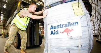 A person in army fatigues pushes a container with the Australian Aid logo on it.