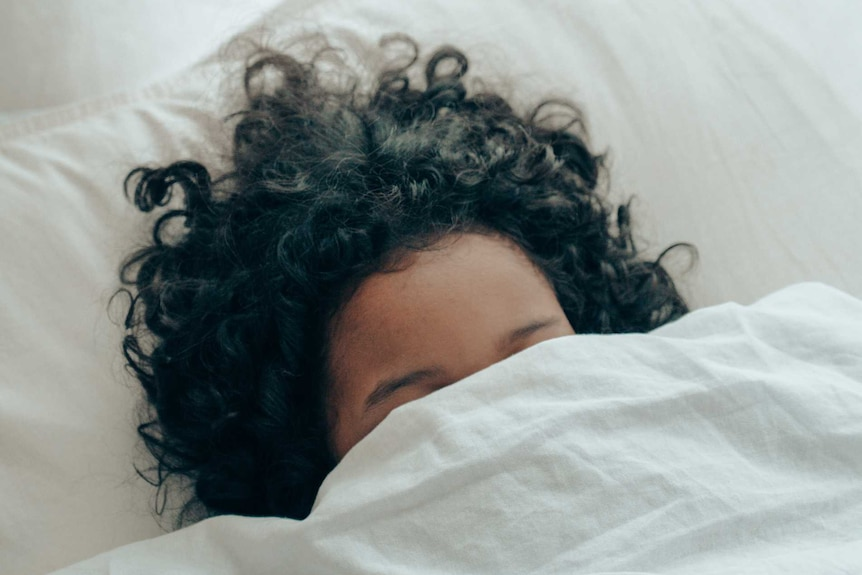 A woman with dark hair, hides her face behind a bed sheet.