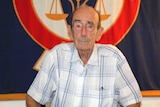 An old man poses for a photo sitting down in front of a blue and red flag.