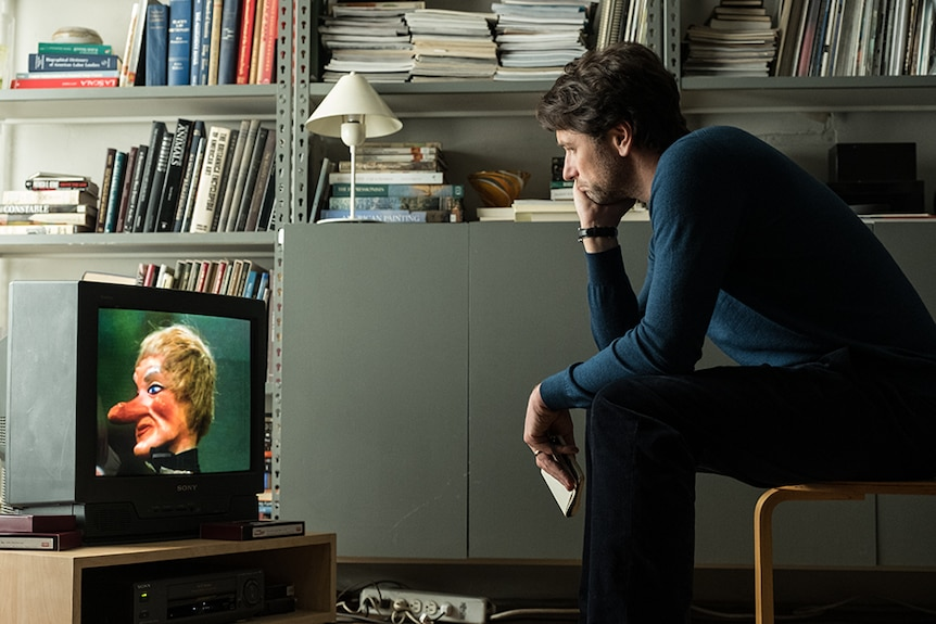A man in navy pullover sits bent over on stool focused on small CRT television set next to a wall of grey metal bookshelves.