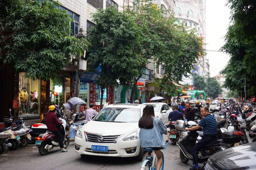 A street with several cars and motorcycles.