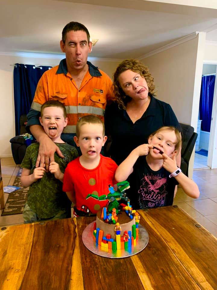 A woman and her husband pose with their three kids behind a kitchen table with a birthday cake