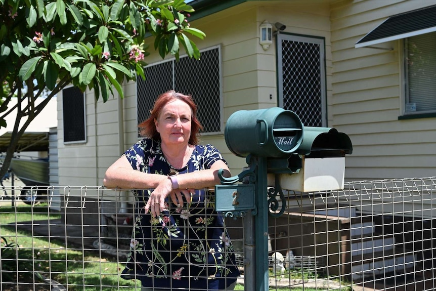 A woman with red hair stands with folded arms leaning on a fence near her letterbox with a frangipani tree in the background.