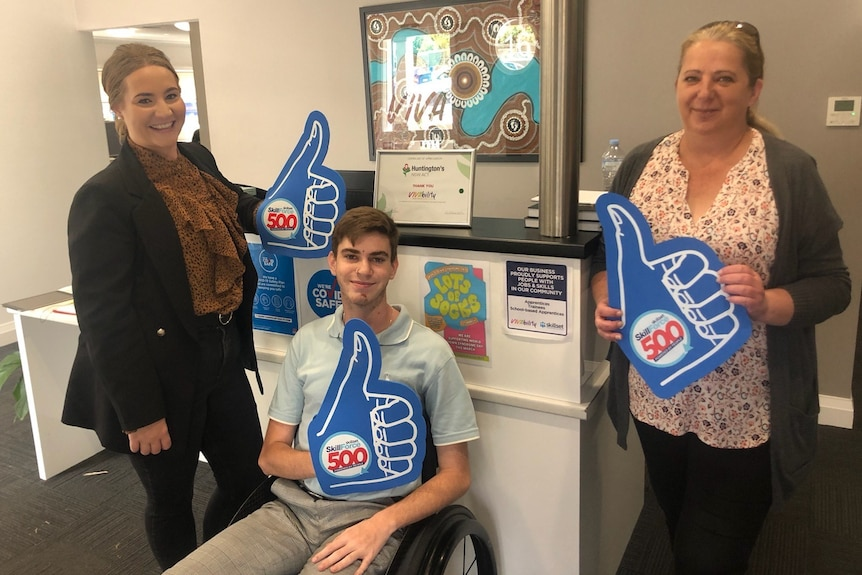 Boy sitting in wheelchair, next to two ladies all holding big blue thumps up signs