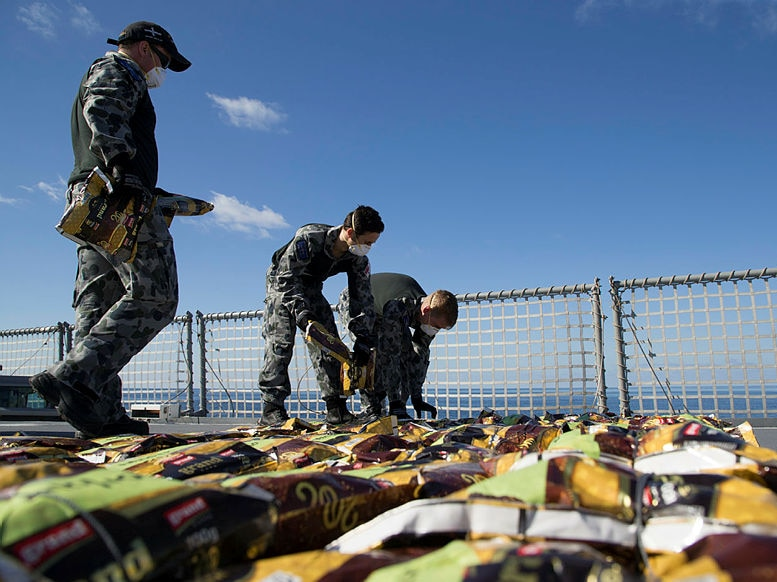Dozens of small packets are lined up on the deck of a ship by men in navy uniforms and breathing masks.