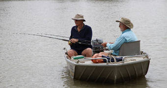 Two older men in a metal dingy fishing