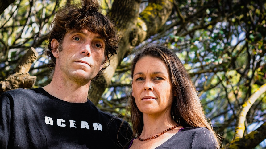 A man and woman stand under a tree on a sunny day looking down at the camera.