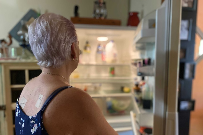 A woman with white hair, in blue top, looks into an open fridge. There are a few items in there, but it is noticeably bear.