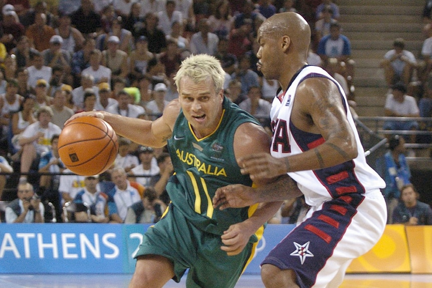 Basketball player dribbling with ball with an opposition player defending him during a game.