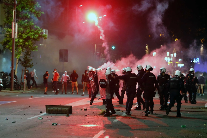 A flare lights up the night sky above  protesters and a group of police in riot gear.