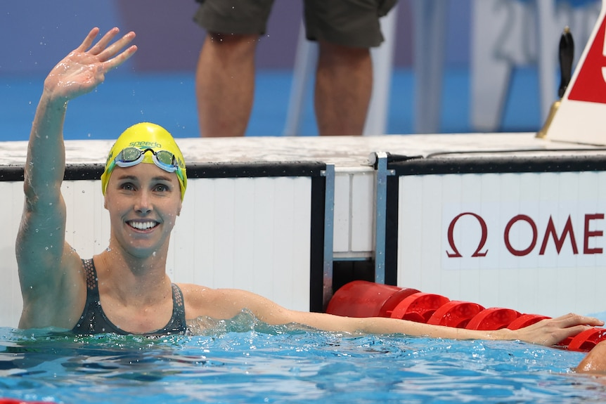 Female swimmer waving to the crowd after winning gold at the Olympics