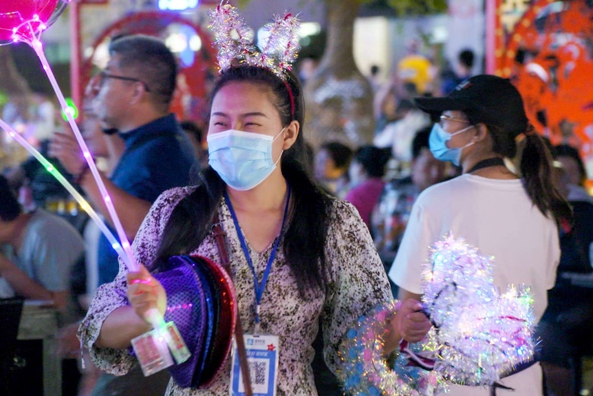 A woman in a face mask holds bunny ears and light-up balloons for sale