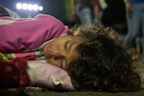 A young girl with wavy brown hair and wearing a pink top sleeps on the footpath with people walking past in the background