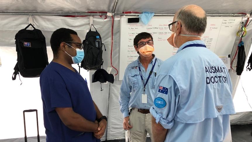 Three men wearing masks talk to each other.