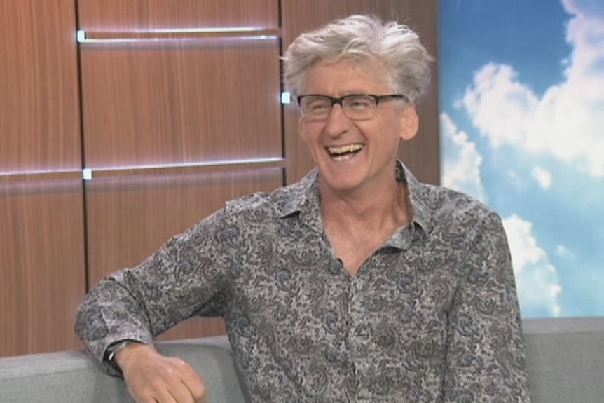 A man laughs while sitting on the set of a television news show.
