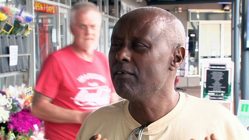 'Lock 'em all up' a white passerby says to an African man being interviewed