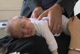 Baby lying at mother's chest receiving chiropractor treatment.