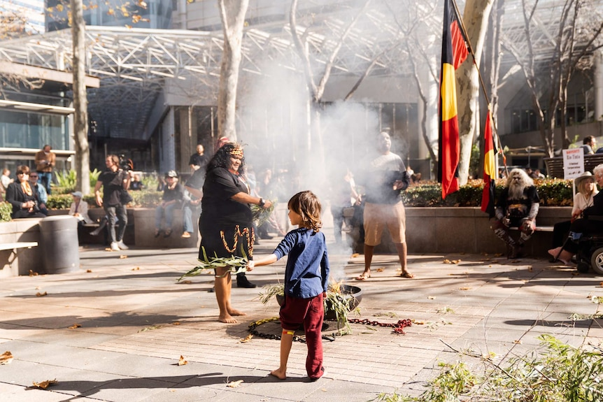 A child stands in front of a smoking ceremony fire outside Rio Tinto offices in Perth CBD.