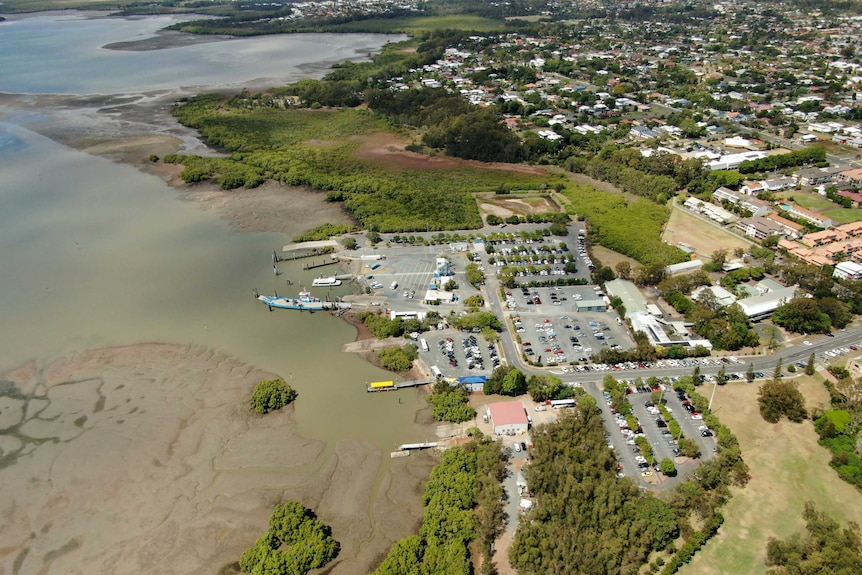 Aerial shot of Toondah Harbour showing the carpark, homes, and the sweep of the coastline.