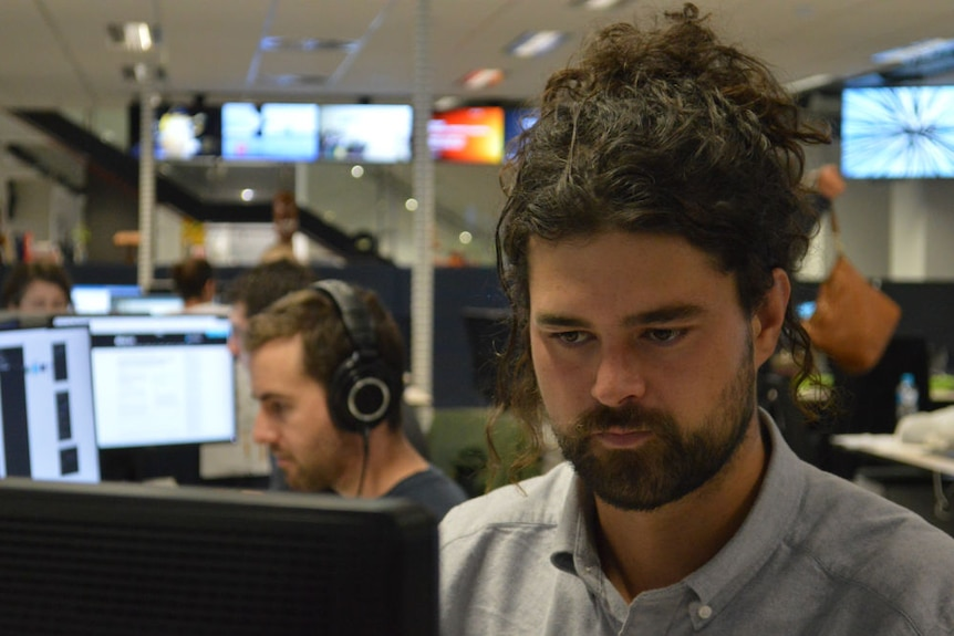 Mantesso sitting at desk in newsroom with man in background wearing headphones.