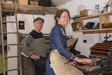 A man and a woman work at vintage presses in an artist's studio