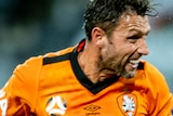 Scott McDonald clenches his teeth and watches the ball as it goes away from his past a player in a blue shirt