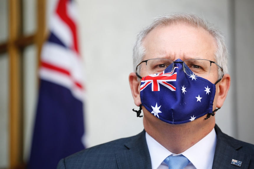 Tight shot of Morrison is staring straight ahead wearing a mask with the Australian flag on it.