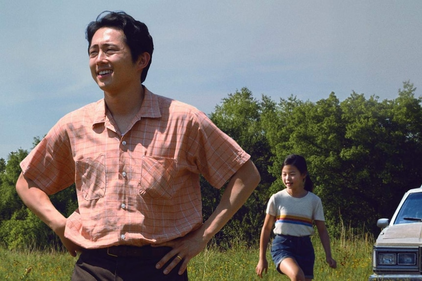 A still from the film Minari with Steven Yeun, patriarch of a family in the foreground, his wife and two kids in the background