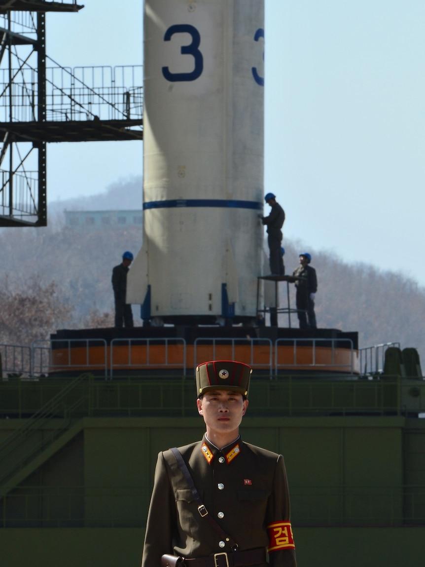 A North Korean soldier guards the Unha-3 rocket