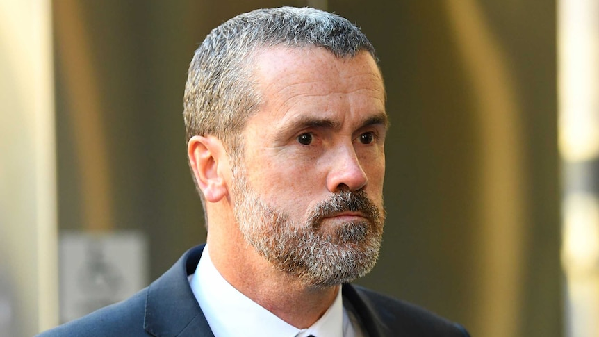 Ross Fowler, a man with short black-and-grey hair and a beard in a suit outside court.