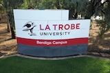 A sign on a green lawn reads 'La Trobe University Bendigo Campus'.