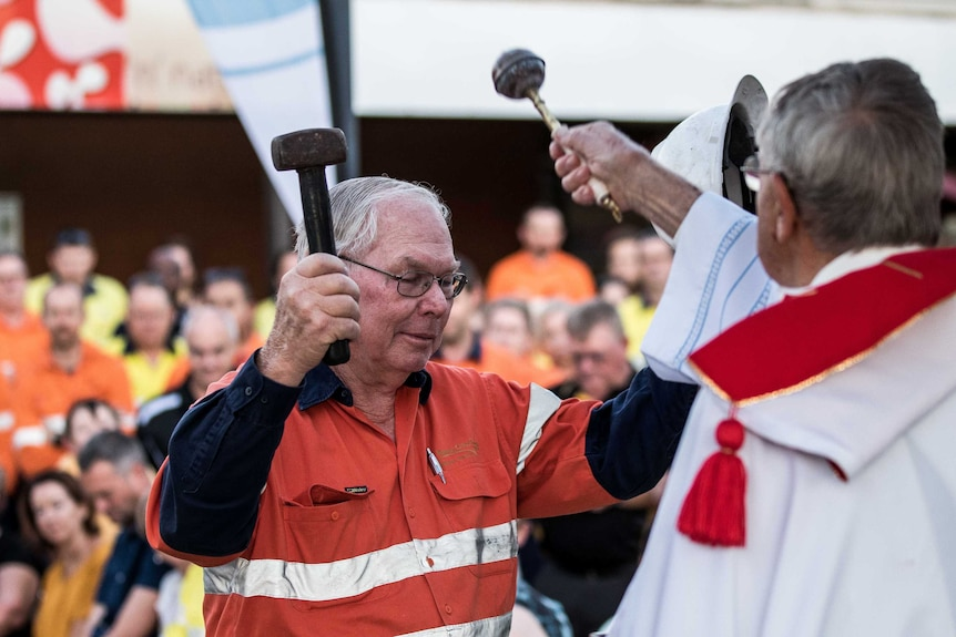 A mine worker wearing high-vis clothing holding a hammer and miner's helmet.