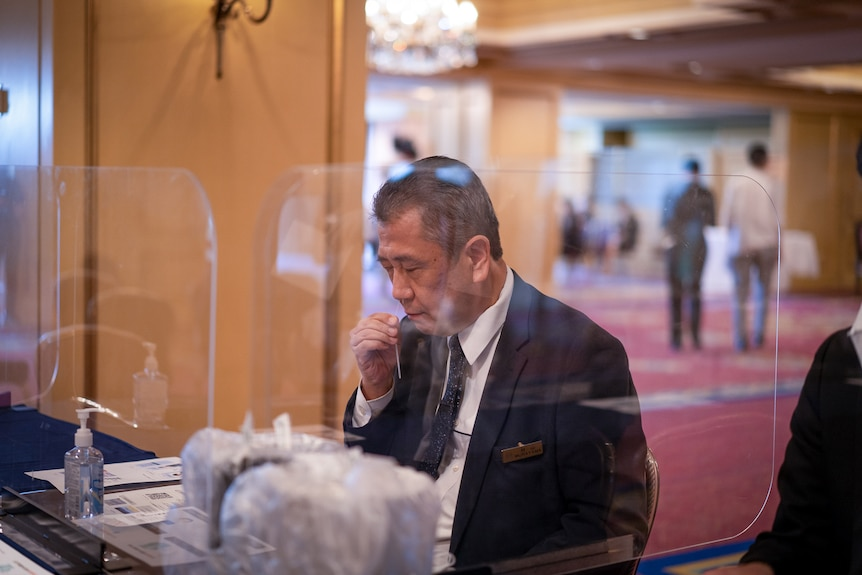 A Japanese man in a suit holds a plastic strip in his nostril