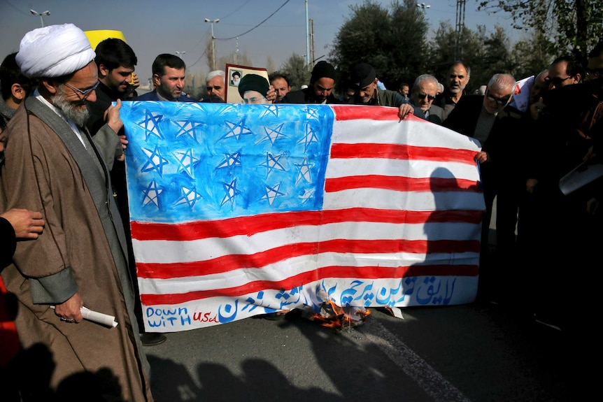 A medium shot of a group of men holding a burning representation of a US flag.